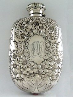 REPOUSSE FLASK, GORHAM   A sterling silver flask, Gorham Manufacturing Co., Providence, Rhode Island, Number 257, circa 1891. Of traditional oblong form, Repousse-chased with blossoms and foliate scroll work, one side centering an oval cartouche which is engraved with a script monogram JAO; length is 7 1/8 inches, weight is 8.50 troy ounces