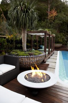 Jamie Durie Contemporary Garden Design Outdoor firepit beside pool with poolside cabana