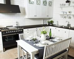 Modern country kitchen in a home in Sandhamm, Sweden. The grey table cloth and green table decor provide just enough variety in the monochrome color palette.
