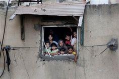 Una familia palestina observa como los servicios de emergencia buscan cadáveres entre los escombros en Gaza, el 21 de julio de 2014. (Foto AP/Khalil Hamra, Archivo)