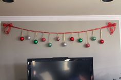 Decorating for Christmas On a Budget | We used the ribbon to make a ornament banner to hang across the top of ... #decoratingonabudget