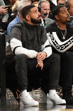 a06045247a8fe1 Drake sits courtside dressed in an OVO track jacket and Nike AF1 sneakers  Drake Fashion
