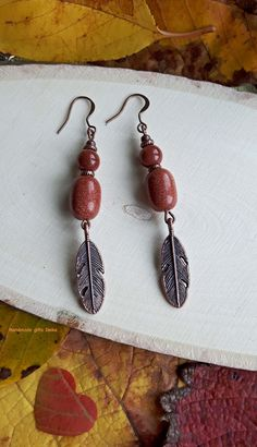 Handmade earrings with sun stone and feathers.