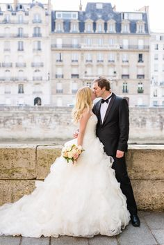 Beautiful Norvegian bride kissing her groom on Ile Saint Louis and having the typical Parisian buildings in the background. Wedding photo captured by Fran Boloni, wedding photographer at Kiss me in Paris More pictures from this wedding on French Wedding Style, here: http://www.frenchweddingstyle.com/family-wedding-in-paris/