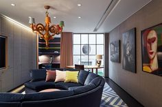 The basement's work den and cinema room, which features a curved velvet-upholstered sofa custom-made by George Smith and a playful 'Patchwork' chandelier from Moooi. A neon-yellow side table from Muuto and a mural above the chimneypiece add colour and warmth in the nursery