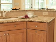 white shaker kitchen has two full walls of windows above base cabinets, micro-tile backsplash and wide-plank oak flooring