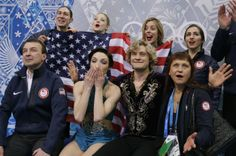 Meryl Davis and Charlie White of the United States, centre, wait in the results area after competing in the team free ice dance figure skati...