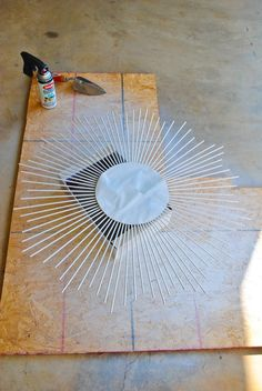 Buy a cheap round mirror and hot glue dowel rods to back of mirror (spray paint rods any color you want). Love this