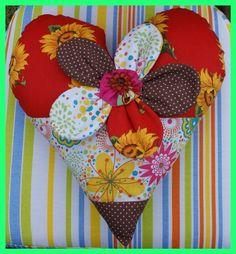 Almofada Coração - Pequena almofada em formato de coração, com mix de tecidos, desenvolvida com técnica de Patchwork. Acabamento em formato de flor, com fuxico e pedraria.    R$45.00