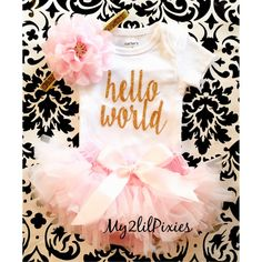 """Perfect Take Home Outfit !  Bring home your little one in our cute """"Hello World"""" GOLD Glitter Onesie , Soft Pink Tutu bloomers and matching headband.  Perfect set for your sweet baby girl   Carters brand Onesie with the words """"Hello  World"""". (Can customize to say another saying, contact me if you have something else in mind)   Perfect for any expectant mommy , a one of a kind newborn going home outfit, use this set when meeting family and friends for the very first time .   All…"""