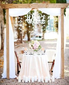 Soft? Sweet? Intimate? All of the above? From the hanging paper flowers to the cloth drape and candles this sweetheart table, captured by AK Studio & Design and designed by Middle Aisle, is all about that ooey gooey thing we call love. Find videos on how to make gorgeous paper flower details here.