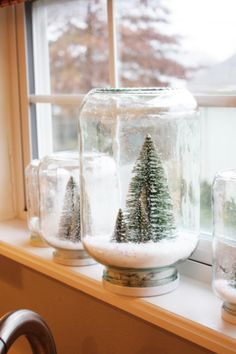 Make your own festive snow globe, really cute. Attach trees with glue to the can's lid's underside. In the Jar add finely shredded fake snow which you can buy at any craft store and a touch of glitter to give it that snow glistening appearence. Lastly flip the Can Lid with the trees upside down and screw on, when securely attached flip upside down and there you have it.
