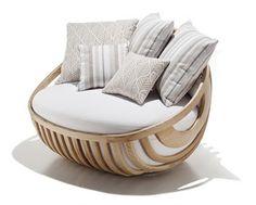 """La colección de muebles de exterior """"Arena"""" de Schoenhuber Franchi nos recuerda a días soleados en la playa o en tu jardín. Hechas de madera curvada de forma natural, la silla, la mesa y el sillón hacen una combinación muy adecuada para cualquier jardín contemporáneo."""