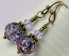 7-8mm Czech Rosebud Amethyst purple luster round beads are complemented with 4mm violet Swarovski crystal beads, antiqued brass daisy bead caps, and rondelles.