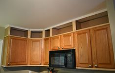 Update the kitchen cabinets with moldings and create the look of open cabinets on the space above.
