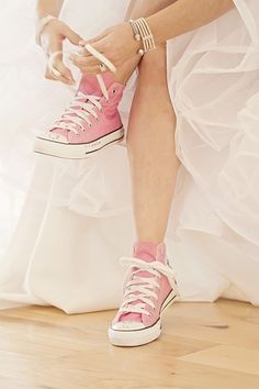Bride in pink converse, wedding dress