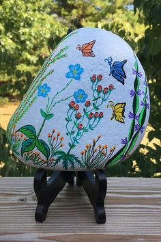 A multicolored fantasy flower garden at night is featured on this unique hand painted rock decoration. This naturally formed river stone weighs about 4.5 pounds and is 6.5 inches tall, 6 inches wide, and 2.5 inches thick. Painted Rocks For Sale, Hand Painted Rocks, River Stones, Etsy Store, Chair, Flowers, Unique, Furniture, Home Decor