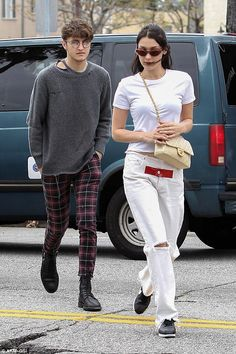 Stylish: Anwar wore a grey sweater with holes throughout and paired it with a pair of burgundy plaid pants