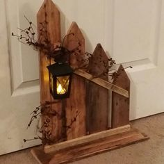 This picket fence primitive country decor is made from reclaimed wood. It has a small lantern with a battery tea candle. A cute addition to your primitive decor. This fence has been stained with a natural wood stain to bring out the woods natural tones. We offer 8 other stain or painted options to choose from. It would look good on a Fireplace, by your front Door or just about anywhere. It measures approx. 22 x 16 Our current processing time is 5 to 10 days. IF you need to put a rush on…
