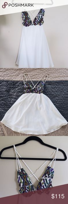 For Love & Lemons Strappy Mini Dress Adorable white dress with adjustable criss-crossing straps in the back. Colorful knit design on the front. Knit material provides padding so you do not need to wear a bra. Beautiful dress, just too small on me! For Love And Lemons Dresses Mini