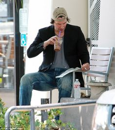 Transfixed: The Matrix star could not take his eyes off his paper even as he sipped at his caffeine