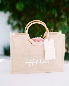 """Molly and Nate wanted to create a vacation experience for their guests and make them feel truly welcomed. Carry Greenjute bags were screen-printed with a big """"Hola!"""" Molly used the font """"Channel Slanted 1"""" for the tote bag's design and the packaging of its contents.Inside each bag was a collection of items sourced by the bride, such as an oversized Turkish towel wrapped in custom ribbon that read """"La Playa."""" Small muslin bags rubber-stamped with various Spanish sayings were also ..."""