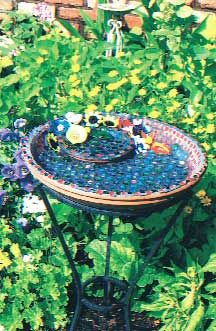 Mosaic Birdbath  Glue two terra-cotta base trays together, a small one inside a large one. Then mosaic them with glass pieces, nuggets and flowers. Grout and seal to keep it from fading.