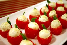 cherry tomatoes stuffed with mozzarella balls, adorned with a basil leaf and sprinkled with garlic salt