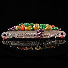 Art Deco fruit bowl brooch - A beautiful Art Deco fruit bowl brooch, platinum, diamond, rock crystal and enamel, ca. 1925. The bowl of rock crystal rimed with a diamond-set border and curved handles, full with enamelled fruits, in the new and daring colour combinations of the 1920s