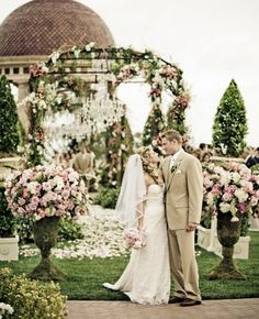 beautiful outdoor ceremony with lots of blush flowers and floral décor with floral arch and chandeliers.