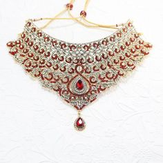 Lohita    Gold based bridal set covered with clear diamante stones and deep red accents. Necklace made from sterling silver base and 3 grams of 24 karat gold.