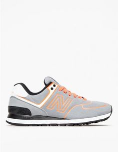The classic 574 silhouette from New Balance with a vibrant pop of neon color. Features flat grey textile uppers with black accents at the midsole and ankle pad with contrasting Dragonfly organe laces, logo and detailing.   	•	Classic 574 trainer silhoue
