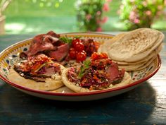 Open-Faced Pitas with Rotisserie Lamb with Pomegranate and Mint, Grilled Tomatoes, and Greek Slaw recipe from Bobby Flay via Food Network