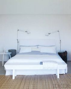 In a bedroom, a modern Gervasoni bed is framed by Tolomeo lamps…