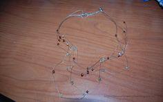 Tante piccole idee realizzate: Un altro groviglio: collana con filo metallico e perline trasparenti, bianche opache e ambra.