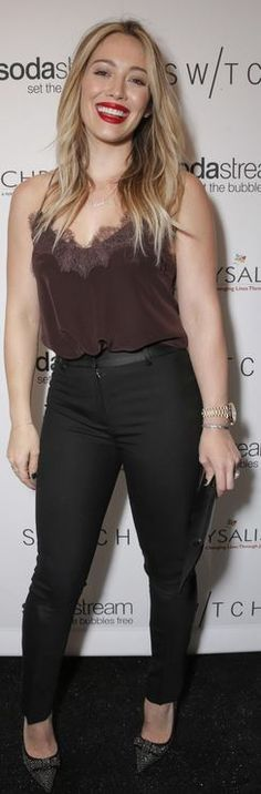 Who made  Hillary Duff's brown lace tank top, black pants, bow studded pumps, and black clutch handbag that she wore in Los Angeles on December 14, 2013?