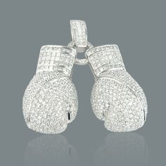 This dazzling and luxuriously unique 14K Gold Diamond Boxing Gloves Pendant weighs approximately 43 grams and showcases exquisite invisibly and channel set princess cut diamonds and pave set round diamonds. Handcrafted to highest standards and featuring 19.95 carats of high quality G color VS clarity diamonds, these fully iced out gold and diamond boxing gloves are available in 14K white, yellow and rose gold and can be customized to meet your specifications.
