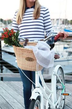 The good life.  Biking by the water with a basket of flowers!