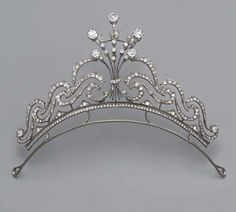 AN ANTIQUE DIAMOND TIARA, property of a lady. The old-cut diamond floral bouquet to the diamond scrolls and collet terminals, mounted in silver and gold, central bouquet detaches to form a brooch, with fittings for necklace, circa 1890, 14.6 cm. wide, in original brown leather fitted case with retailer's stamp Gebr. Sommé Nachf., Hof-Juweliere, Sr. Maj. d. Kaisers, Breslau.
