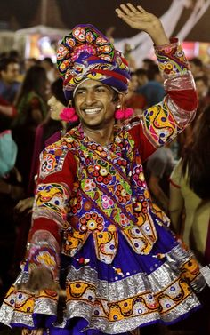 An Indian man wearing traditional attire performs Garba during Navratri festival, in Ahmedabad, India, Garba is a folk dance in which participants move in a circle while clapping. Navaratri, the festival of nights, lasts for nine days, with three days each devoted to the worship of Durga, the goddess of valor, Lakshmi, the goddess of wealth, and Saraswati, the goddess of knowledge. Feasting and fasting takes over normal . (AP Photo/Ajit Solanki)