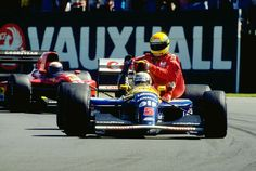 Nigel Mansell gives Ayrton Senna a lift back to the Paddock at Silverstone. Senna had run out of fuel while Mansell won the race, so the lift occurred on Mansell's Victory Lap. 1991.