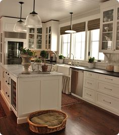 One of my favorite kitchens: White drawers instead of lower cabinets, glass panel upper cabinets, wainscoting back splash and windows.