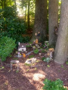A fairy village tucked into the tree roots. Fairy/gnome doors lead inside the trees, a blue gravel path leads throughout town, a bridge, twig fence with arbor, miniature birdhouses, and windows into the trees.