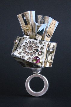 "Tzu-Ju Chen |Chartres Cathedral, ring (front), size 6.5, ring crown is 2.5 x 1.5 x 2 inches.  Sterling silver, photographs, museum boards, and tourmalines. 2005  photo by Christian Cutler     Laminated photographs, sterling silver  ""My works explores the conceptual play of material and meaning. Travel photography and  vintage snapshots serve as mementos that embody the present reality."