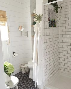 Subway tile on sink, far wall and shower. Drywall or shiplap on other end wall and washer/dryer nook.