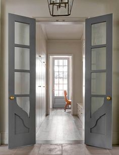 Gray bi-fold doors with glass panels open to a long and narrow mudroom filled with floor to ceiling light gray cabinets facing a light gray mudroom bench as well as a small home office filled with a built-in desk and an orange chair. - May 05 2019 at Narrow French Doors, Bifold French Doors, French Closet Doors, Internal French Doors, Double Doors, Bi Fold Doors Internal, Glass Panel Door, Glass Panels, Glass Doors