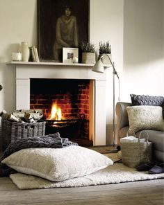 Cozy fire, big cabled blanket, wooly pillow and rug.