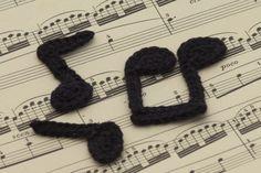 Drei gehäkelte Noten auf einem Notenblatt - Three crocheted music notes on a sheet of music
