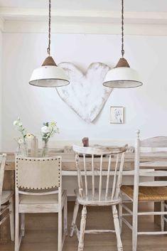 Houten eettafel met verschillende stoelen in wittinten. De lampen passen er perfect bij.