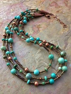 This necklace is made using three hand-beaded strands containing different shapes and types of turquoise, copper and antiqued glass seed beads. The strands come together with two copper cones. Approx